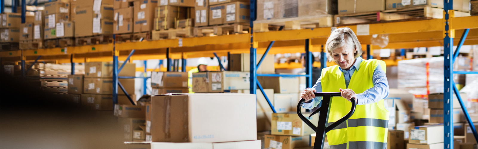 senior-woman-warehouse-worker-pulling-a-pallet-truck-with-boxes-picture-id964380614